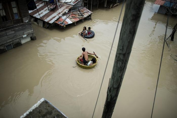 "<i>เด็กๆ ใช้กาละมังและยางรถเพื่อข้ามถนนที่น้ำท่วมสูงภายหลังถูกไต้ฝุ่น ""มังคุด"" พัดกระหน่ำ ที่เมืองคาลุมปิต จังหวัดบูลาคาน ประเทศฟิลิปปินส์ เมื่อวันอาทิตย์ (16 ก.ย.) </i>"