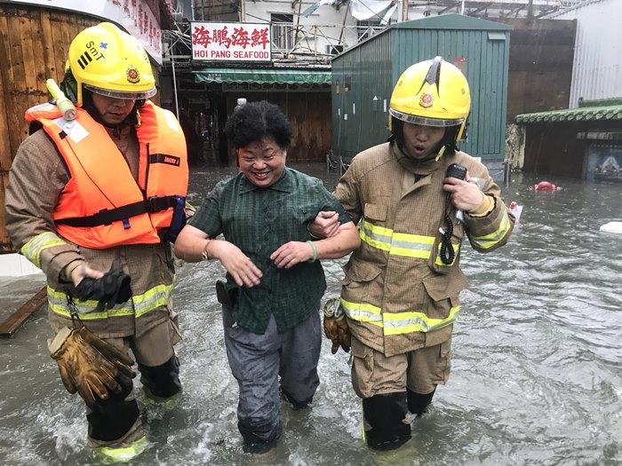 """<i>เจ้าหน้าที่ดับเพลิงช่วยเหลือหญิงผู้หนึ่งเดินข้ามพื้นที่น้ำท่วมในหมู่บ้าน เหลย ยู มุน  จากฤทธิ์เดชของไต้ฝุ่น """"มังคุด"""" ที่พัดเข้าฮ่องกง </i>"""