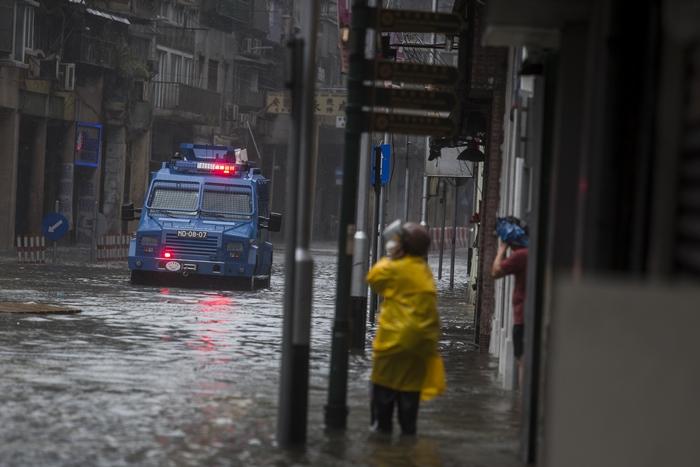 """<i>รถตำรวจขับผ่านบริเวณน้ำท่วมขณะประกาศเตือนประชาชนเรื่องคลื่นพายุโถมซัดใส่ฝั่ง ระหว่างที่ไต้ฝุ่น """"มังคุด"""" พัดเข้ามาเก๊า เมื่อวันอาทิตย์ (16 ก.ย.) </i>"""