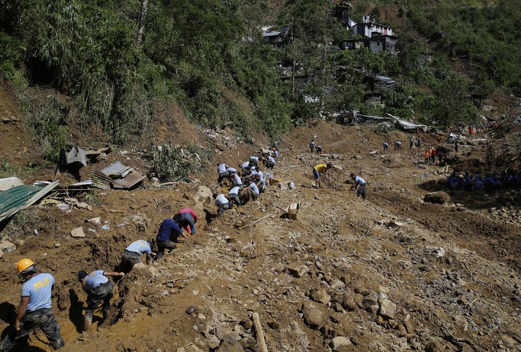 <i>มีเจ้าหน้าที่กู้ภัยฟิลิปปินส์จำนวนมากในวันจันทร์ (17 ก.ย.) ช่วยกันขุดค้นหาเหยื่อซึ่งถูกฝังใต้กองดินโคลนถล่ม ที่หมู่บ้านในเขตเมืองอิโตกอน จังหวัดเบงเกต </i>