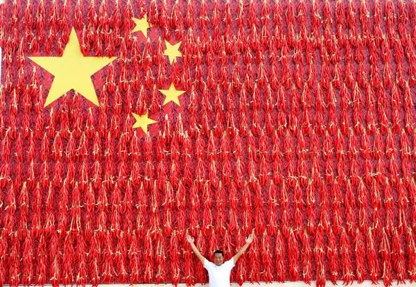 ต้องรักชาติ...หนุ่มจีนจัดท่าทางหน้าแบบธงชาติจีนที่ใช้พริกมาออกแบบ ในอำเภอเมิ่งจิน มณฑลเหอหนัน วันที่ 21 ก.ย. 2018 (ภาพ รอยเตอร์ส)