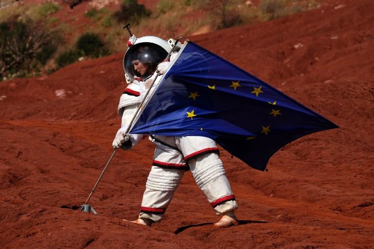 พิธีกรจากสถานีโทรทัศน์ในฝรั่งเศส ลงทุนสวมชุดอวกาศเพื่อถ่ายทำรายการที่เมืองวิทอเลอส์ (Vitrolles) ใกล้เมืองมาร์กเซย (Marseille) ทางตอนใต้ของฝรั่งเศส (BORIS HORVAT / AFP )