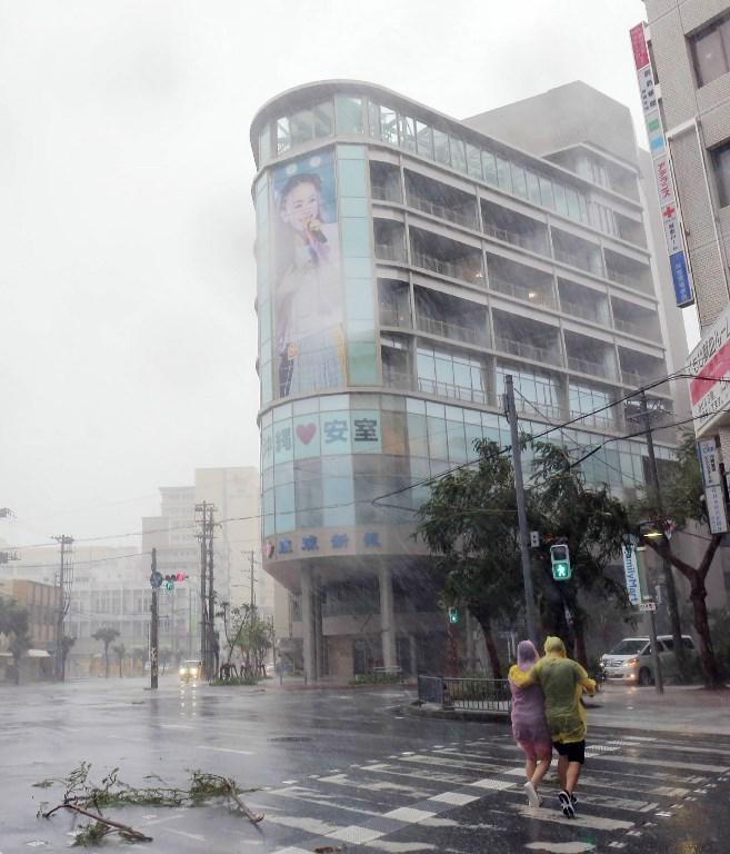 ชาวญี่ปุ่นเดินฝ่าพายุข้ามถนนในเมืองนาฮา (Naha) หลังจากที่ไต้ฝุ่นจ่ามีเคลื่อนตัวเข้าซัดถล่มเกาะโอกินาวาในวันนี้ (29 ก.ย.)