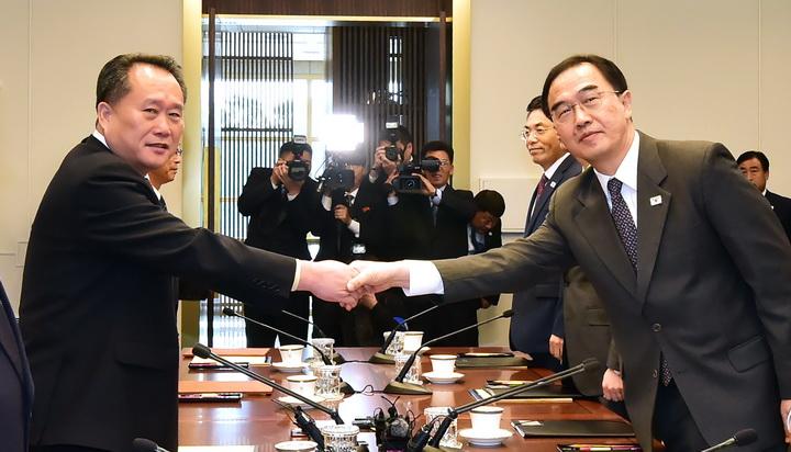 """โช มยอง-กยอน รัฐมนตรีกระทรวงรวมชาติเกาหลีใต้ (ขวา) จับมือกับ รี ซอน-กวอน ประธานคณะกรรมการการรวมชาติอย่างสันติของเกาหลีเหนือ (ซ้าย) เมื่อวันจันทร์ (15 ต.ค.) ระหว่างพบปะเจรจากันทางฝั่งของเกาหลีใต้ที่หมู่บ้านสงบศึก """"ปันมุนจอม"""" ในเขตปลอดทหารที่กั้นระหว่างสองเกาหลี"""