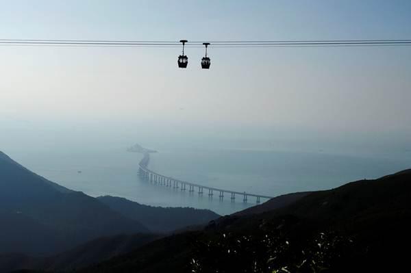 รถเคเบิลจากลันเตาเคลื่อนเข้ามายังสะพานเชื่อมฮ่องกง-จูไห่-มาเก๊า ภาพวันที่ 21 ต.ค. 2018 (ภาพ รอยเตอร์ส)