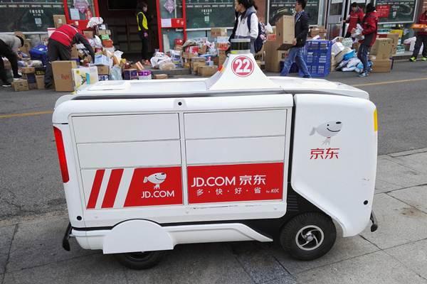 หุ่นยนต์ขนส่งสินค้าไร้คนขับของค่ายอีคอมเมิร์ชรายใหญ่  JD.com นอกศูนย์โลจิสต์ติกส์ของ JD.com ในปักกิ่งวันที่ 12 พ.ย. ทั้งนี้ มหกรรมช้อปปิ้งวันคนโสด ยังช่วยดันยอดขายของแบรนด์อีคอมเมิร์ชรายอื่นๆด้วย (ภาพ รอยเตอร์ส)