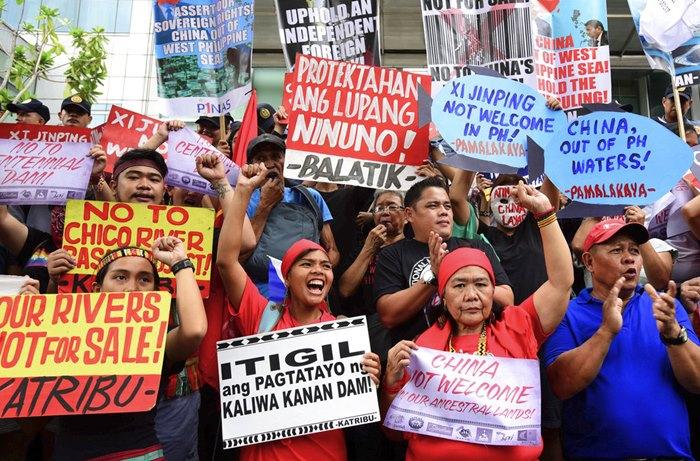 <i>กลุ่มผู้ประท้วงชูป้ายและตะโกนคำขวัญต่อต้านการมาเยือนฟิลิปปินส์ของประธานาธิบดีสี จิ้นผิง ขณะชุมนุมอยู่หน้าสำนักงานการทูตของจีน เมื่อวันอังคาร (20 พ.ย) </i>