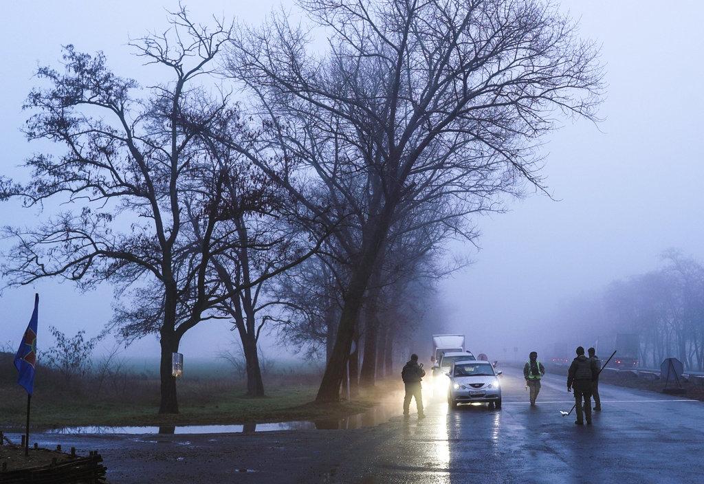 <i>ทหารและตำรวจของยูเครน หยุดรถคันหนึ่งเพื่อขอตรวจเอกสารที่ด่านตรวจแห่งหนึ่งนอกเมืองมารีอูปัล  เมืองท่าของยูเครนซึ่งอยู่ติดทะเลอะซอฟ  เมื่อวันอังคาร (27 พ.ย.)  ขณะประธานาธิบดีเปโตร โปโรเชนโก ของยูเครน กำลังออกมาโวยวายว่ารัสเซียเตรียมจะทำสงครามใหญ่เล่นงานยูเครน </i>