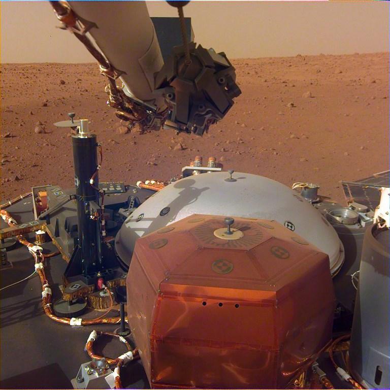 กล้องบนแขนกลของยานอินไซต์เผยเครื่องมือต่างๆ บนพื้นยานอินไซต์ และพื้นผิวของดาวอังคารบริเวณ เอลิเซียม พลานิเชีย และตอนนี้เราสามารถฟังเสียงทุ้มต่ำของอังคารได้เป็นครั้งแรก (Elysium Planitia)  HO / NASA/JPL-CALTECH / AFP