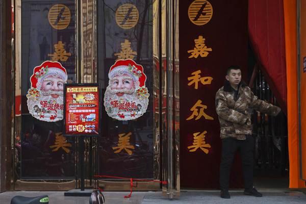 หน้าประตูร้านค้าที่ถูกตกแต่งด้วยภาพซันตาคลอสในจางจยาโข่ว มณฑลเหอเป่ยเมื่อวันที่ 22 ธ.ค. (ภาพ เอพี)