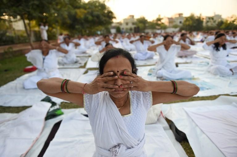 ภาพกิจกรรมโยคะที่อินเดีย ทั้งนี้มีความเชื่อว่าการออกกำลังกายช่วยลดโอกาสเป็นอัลไซเมอร์ (SAM PANTHAKY / AFP)