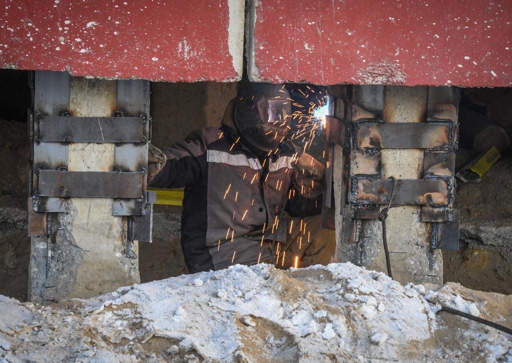 ช่างก่อสร้างกำลังเชื่อมเสริมความแข็งแรงให้โครงสร้างอาการที่แตกร้าวในเมืองยาคุตสค์ (Mladen ANTONOV / AFP)