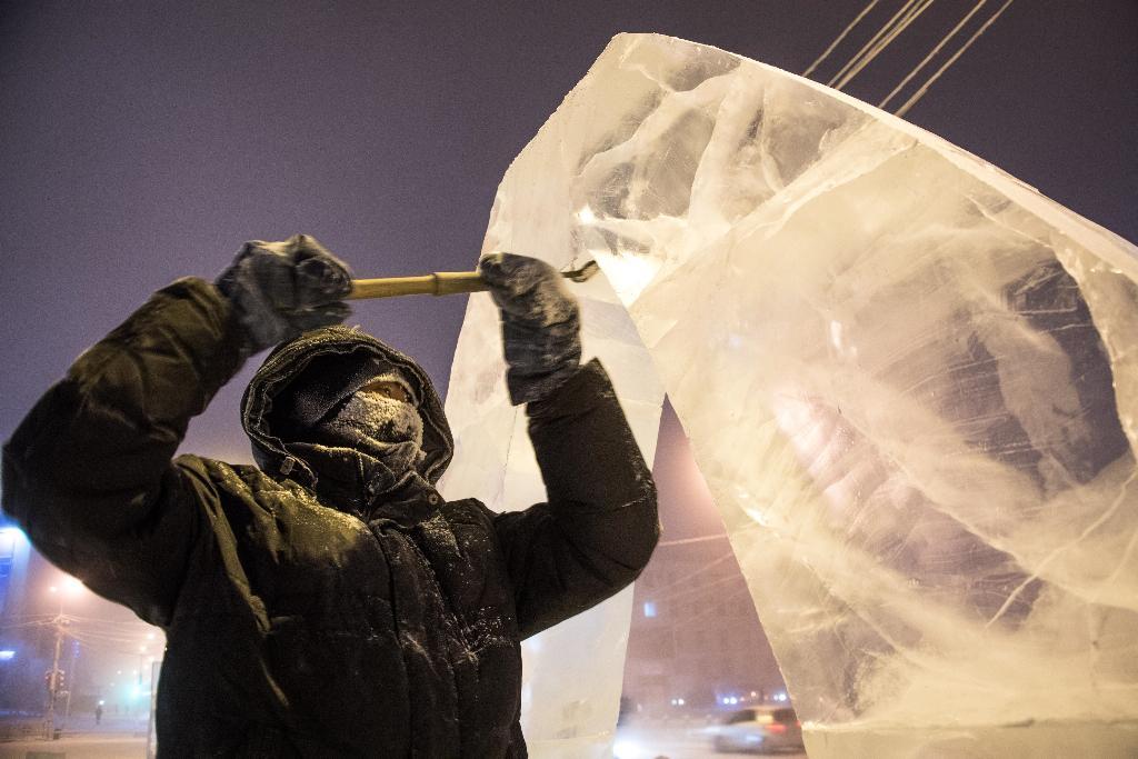 ภาพศิลปินกำลังแกะสลักน้ำแข็งสร้างปะติมากรรมที่เมืองยาคุตสค์ ขณะอุณหภูมิ - 40 องศาเซลเซียส   (Mladen ANTONOV / AFP)