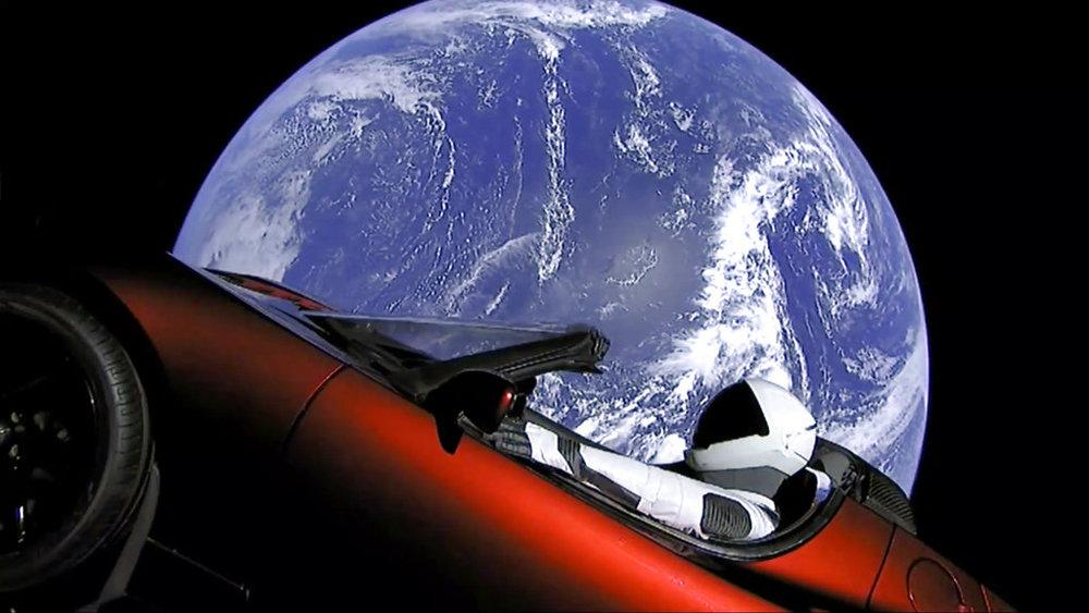 """<i>ภาพจากวิดีโอของ สเปซเอ็กซ์ แสดงให้เห็นชุดมนุษย์อวกาศในรถสปอร์ต """"เทลซา"""" สีแดง ของ อีลอน มัสก์ ซึ่งถูกขึ้นสู่อวกาศ ระหว่างการทดสอบยินครั้งแรกของจรวดฟัลคอน เฮฟวี เมื่อต้นเดือนกุมภาพันธ์ 2018 </i>"""