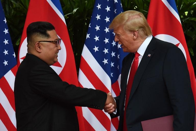 """<i>คิม จองอึน ผู้นำเกาหลีเหนือ กับ ประธานาธิบดีโดนัลด์ ทรัมป์ ระหว่างการประชุมซัมมิต """"ครั้งประวัติศาสตร์"""" ที่สิงคโปร์ เมื่อเดือนมิถุนายน 2018 </i>"""