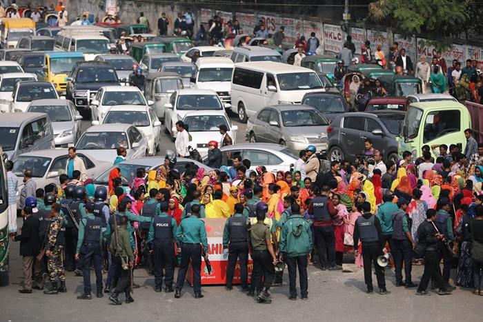 ตำรวจบังกลาเทศอยู่ท่ามกลางพนักงานโรงงานทอผ้ากำลังปิดถนนนประท้วงขอขึ้นค่าแรงในกรุงธากา บังกลาเทศ วันเสาร์(12 ม.ค) ภาพรอยเตอร์