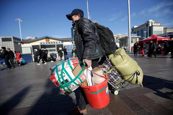 ผู้โดยสารหอบหิ้วสัมภาระข้าวของ มาถึงสถานีรถไฟในกรุงปักกิ่งในวันแรกของการเดินทางช่วงเทศกาลตรุษจีน วันที่ 21 ม.ค. 2019 (ภาพ รอยเตอร์ส)