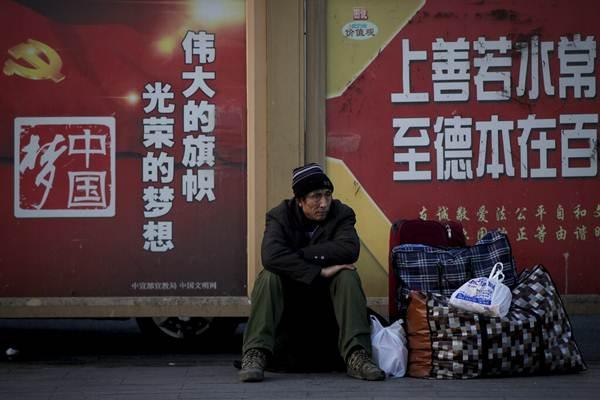 คนงานต่างถิ่นนั่งพันหน้าป้ายโฆษณาชวนเชื่อของรัฐบาลที่สถานีรถไฟปักกิ่ง ในวันแรกของการเดินทางช่วงเทศกาลตรุษจีน วันที่ 21 ม.ค. 2019 (ภาพ เอพี)
