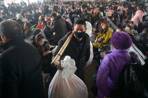 ชายจีนหาบสัมภาระของตนขณะเดินฝ่าคลื่นผู้โดยสารที่สถานีรถไฟจยาซิง มณฑลเจ้อเจียงในวันแรกของการเดินทางช่วงเทศกาลตรุษจีน วันที่ 21 ม.ค. 2019 (ภาพ รอยเตอร์ส)