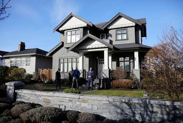 กลุ่มเจ้าหน้าที่จากบริษัทรักษาความปลอดภัยเอกชน ยืนอยู่นอกบ้านที่ครอบครัวเมิ่ง หวั่นโจว ประธานฝ่ายการเงินหัวเว่ย อาศัยอยู่ในแวนคูเวอร์ ประเทศแคนาดา  ภาพ 28 ม.ค. (ภาพ รอยเตอร์ส)