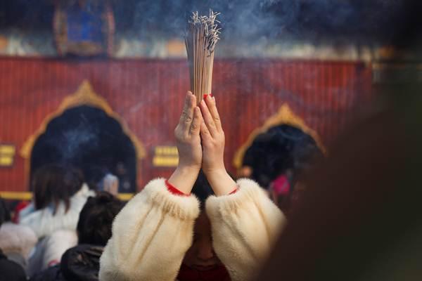 สาวจีนจุดธูปอธิษฐานสวดมนต์ขอพรให้โชคดีมีชัยที่วัดลามะกรุงปักกิ่ง ในวันที่ 5 ก.พ. ซึ่งเป็นวันปีใหม่ตามปฏิทินจันทรคติจีน (ภาพ รอยเตอร์ส)