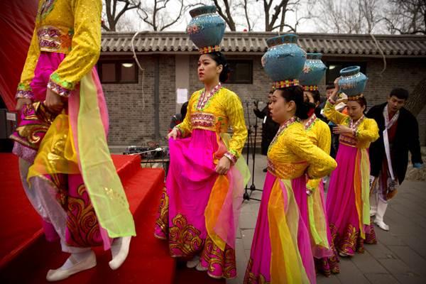 สาวนักแสดงเต้นระบำกำลังขึ้นเวทีที่งานวัดที่หลงถันพาร์ค ปักกิ่ง วันที่ 6 ก.พ. (ภาพ เอพี)