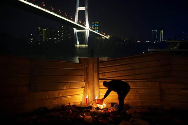 ชายจีนเผากระดาษเงินกระดาษทองริมแม่น้ำแยงซีเกียง นครฉงชิ่งในวันสุกดิบหรือวันไหว้ของวันขึ้นปีใหม่ตามปฏิทินจันทรคติจีน (ภาพ รอยเตอร์ส)