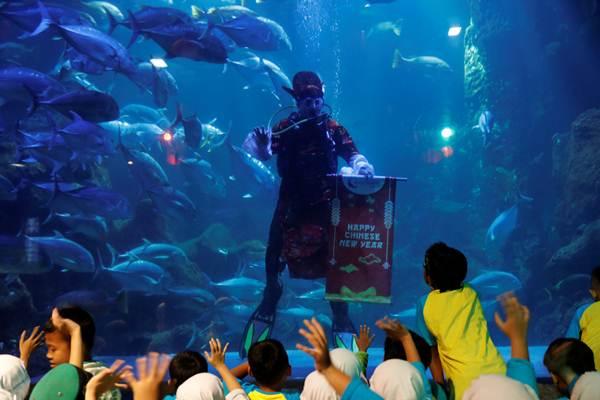 นักแสดงโบกมือให้เด็กๆระหว่างการแสดงเชิดสิงโตใต้น้ำฉลองตรุษจีนที่ซีเวิล์ด มารีน พาร์ค ในกรุงจาการ์ตา อินโดนีเซีย (ภาพ รอยเตอร์ส)
