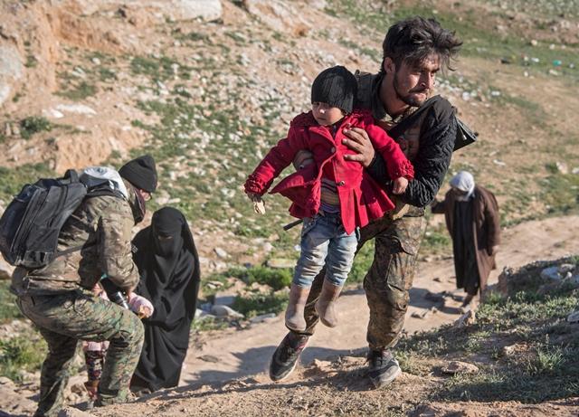 นักรบของกองกำลังประชาธิปไตยซีเรีย (เอสดีเอฟ) ที่สหรัฐฯ หนุนหลังกำลังช่วยผู้หญิงและลูกๆ ของพวกเธอบริเวณที่โล่งแห่งหนึ่ง หลังจากพวกเขาหลบหนีจากพื้นที่บากูซในจังหวัดเดอีร์อัสซอร์ทางตะวันออกของซีเรีย (12 ก.พ)