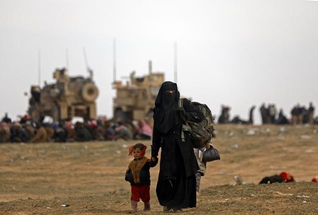 พลเรือนที่หลบหนีจากแหล่งกบดานบากูซของกลุ่มไอเอสกำลังเดินในที่โล่งแห่งหนึ่ง (13 ก.พ.) ในระหว่างปฏิบัติการของกองกำลังประชาธิปไตยซีเรีย (เอสดีเอฟ) เพื่อขับไล่นักรบญิฮาดกลุ่มรัฐอิสลาม (ไอเอส) หลายร้อยคนออกจากพื้นที่นี้ ในจังหวัดเดอีร์อัสซอร์ของซีเรีย