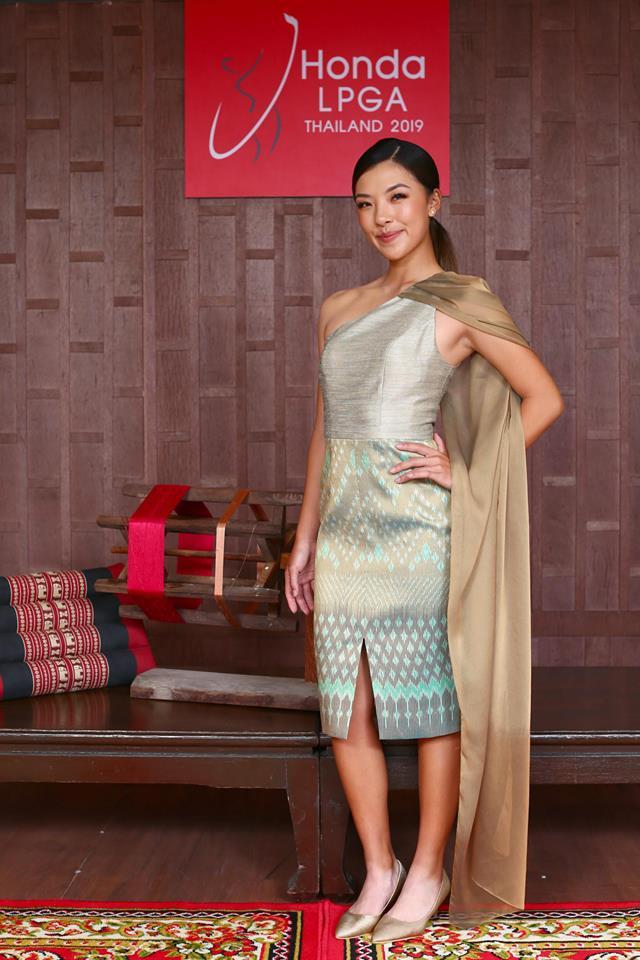 มุนี เหอ โปรกอล์ฟสาวจากจีน แสดงถึงความหรูหราทันสมัยด้วยชุดเดรสเข้ารูปผ้าไหมมัดหมี่ลายดาวเจ็ดสายในโทนสีทองเขียว เพิ่มความพลิ้วไหวด้วยชายผ้าตกแต่งไหล่ข้างให้ความรู้สึกอ่อนหวาน แต่ยังเคลื่อนไหวได้อย่างคล่องตัวในทุกอิริยาบท