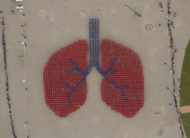 กลุ่มผู้เข้าร่วมรณรงค์ขจัดมลพิษอากาศ กว่า 1,500 คน สวมชุดสีฟ้าและสีแดง จัดขบวนแปรรูปปอดมนุษย์ ระหว่างการแข่งขันชิงสถิติโลก Guinness World Record ในปรุงปักกิ่ง เมื่อเดือนพ.ย.ปี 2015 ทั้งนี้ฝุ่นละอองขนาดเล็ก PM2.5 สามารถแทรกเข้าสู่ปอด ทำลายสุขภาพ (แฟ้มภาพ รอยเตอร์ส)