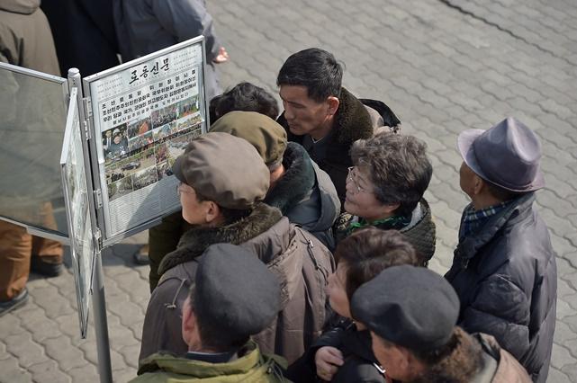 ประชาชนชาวเกาหลีเหนือกำลังอ่านข่าวประธานาธิบดี คิม จองอึน ในงานประชุมซัมมิตที่ฮานอย
