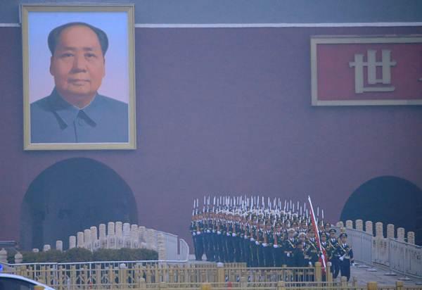 กลุ่มทหารจากกองทัพปลดแอกประชาชนจีน หรือพีแอลเอ เข้าร่วมพิธีเชิญธงประจำชาติขึ้นสู่เสา ก่อนพิธีเปิดการประชุมสภาผู้แทนประชาชนจีน หรือสภาเอ็นพีซี ในวันที่ 5 มี.ค. (ภาพ รอยเตอร์ส)
