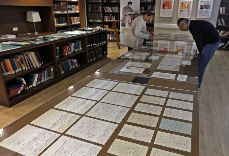 ผู้หญิงและผู้ชายกำลังเพ่งพิจารณาเอกสารลายมือไอน์สไตน์ (MENAHEM KAHANA / AFP)
