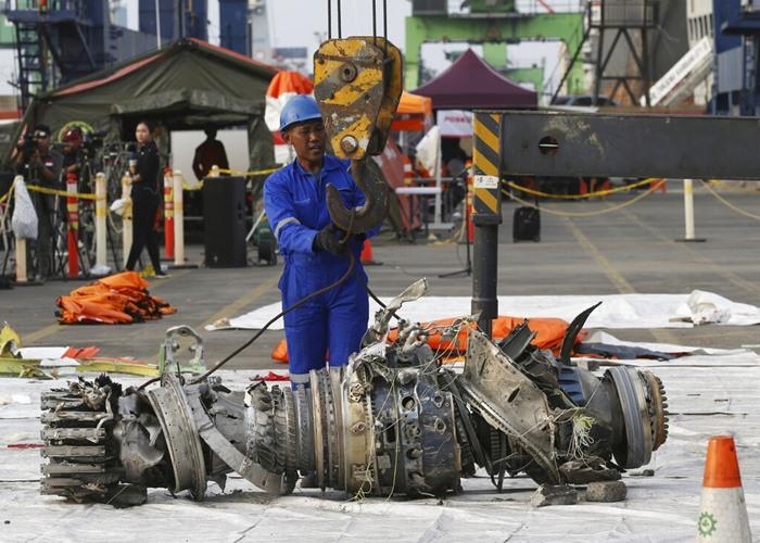 <i>(ภาพจากแฟ้มถ่ายเมื่อ 4 พ.ย.2018) ขณะเจ้าหน้าที่นำเอาเครื่องยนต์ที่กู้ขึ้นมาจากโบอิ้ง 737 แม็กซ์ 8 ของสายการบินไลอ้อนแอร์ซึ่งตกลงในทะเล ขึ้นมาที่ท่าเรือ </i>