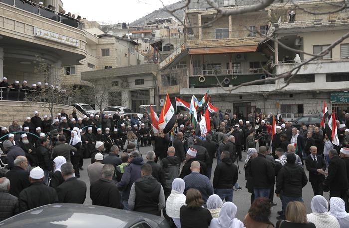 <i>ชาวบ้านซึ่งพำนักอาศัยในที่ราบสูงโกลาน โบกธงชาติซีเรียและธงของชาวดรูซ ขณะพวกเขาประท้วงเรื่องที่ทรัมป์จะรับรองว่าโกลานเป็นของอิสราเอล ณ หมู่บ้านมัจดัล ชามส์ ในเขตที่ราบสูงโกลานที่อิสราเอลยึดครองอยู่ (ภาพถ่ายเมื่อ 23 มี.ค.) </i>