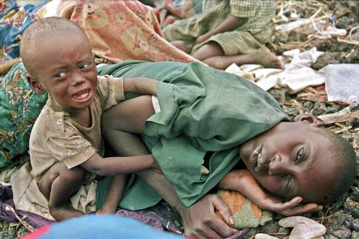 <i>(ภาพจากแฟ้มถ่ายเมื่อ 27 ก.ค. 1994) เด็กผู้ลี้ภัยชาวฮูตูผู้หนึ่งพยายามปลุกแม่ซึ่งหลับไปจากอาการโรคร้าย ในค่ายผู้ลี้ภัยมูนิกี นอกเมืองโกมา ประเทศซาอีร์ ซึ่งปัจจุบันเปลี่ยนชื่อเป็น สาธารณรัฐประชาธิปไตยคองโก </i>