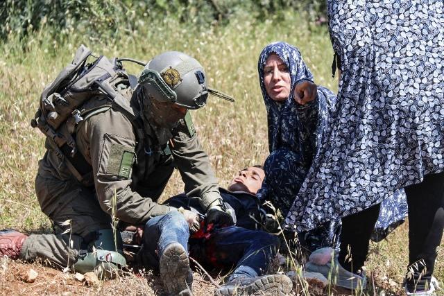 ภาพทหารอิสราเอลกำลังทำการปฐมพยาบาล โอซามา อาลี อัลบาดัน ชาวปาเลสไตน์วัย 16 ปี หลังเขาถูกยิงโดยกองกำลังอิสราเอล