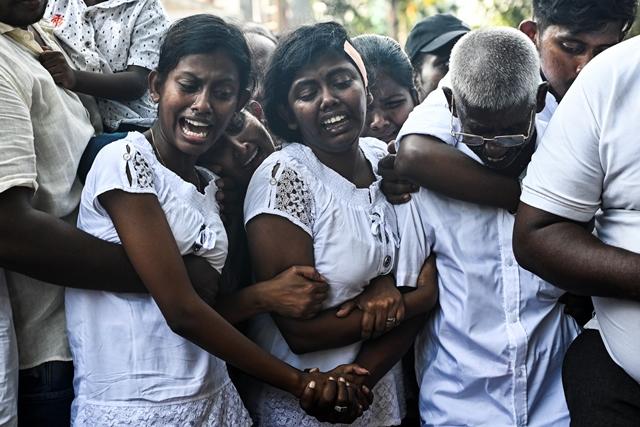 ญาติๆ กำลังเศร้าโศกในระหว่างพิธีฝังศพของเหยื่อเหตุระเบิดที่สุสานแห่งหนึ่งในกรุงโคลัมโบ (25 เม.ษ.)