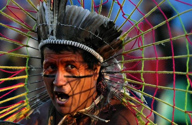 ชายพื้นเมืองคนหนึ่งกำลังประกอบพิธีกรรมในค่ายประท้วงในเมืองบราซิเลียของบราซิล (25 เม.ษ.)