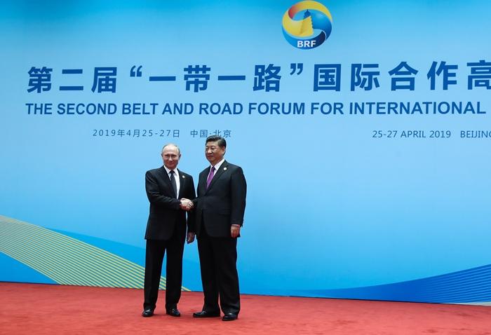 <i>ประธานาธิบดีสี จิ้นผิง ของจีน (ขวา) จับมือกับประธานาธิบดีวลาดิมีร์ ปูติน แห่งรัสเซีย ระหว่างพิธีต้อนรับในวันสุดท้ายของการประชุมแถบและเส้นทาง เมื่อวันเสาร์ 27 เม.ย. </i>