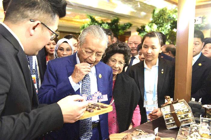 นายมหาเธร์ โมฮัมหมัด นายกรัฐมนตรีมาเลเซีย เยี่ยมชมและชิมช็อกโกแลตทุเรียนในเทศกาลทุเรียนมาเลเซีย ที่กรุงปักกิ่งเมื่อวันที่ 27 เมษายน 2562