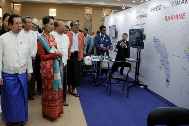 นางอองซานซูจี ที่ปรึกษาแห่งรัฐ ชมแผนภาพที่จัดแสดงโครงการการลงทุนในรัฐยะไข่. -- Reuters.