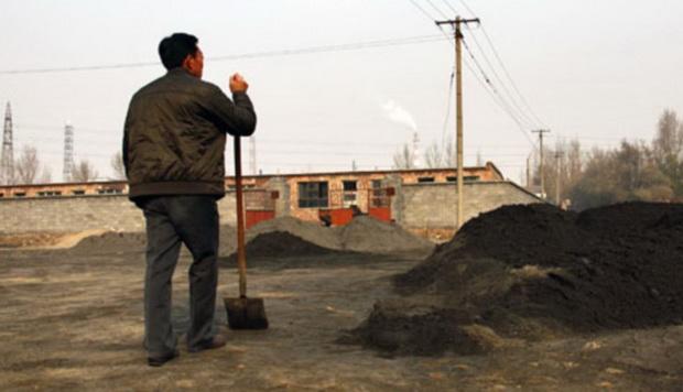 (แฟ้มภาพ) ชาวบ้านคนหนึ่งกำลังมองไปที่โรงงานถลุงแรร์เอิร์ธ ระหว่างพักเบรคจากการตักสินแร่ที่บรรจุแร่โลหะหายาก ในหมู่บ้านซินกวง ประเทศจีน