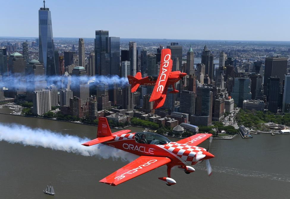 """งานแสดงแอร์โชว์ของสหรัฐฯ ซึ่งนักบินผาดโผนของทีมออราเคิลคือ  ณอน ดี. ทัคเกอร์(Sean D. Tucker) และเจสซี แพนเซอร์(Jessy Panzer) (ล่าง)กำลังขับเครื่องบินสีแดงที่มีสัญลักษณ์ออราเคิลติดอยู่ด้านข้าง บินเหนือแม่น้ำฮัดสันผ่านตึกเวิลด์เทรดเซนเตอร์ในวันพุธ(22 พ.ค)ก่อนงานแสดงการจัดการแสดงการบิน """"เบธเพจแอร์โชว์""""( Bethpage Air Show )ที่โจนส์ บีช( Jones Beach) ในช่วงวันหยุดสุดสัปดาห์วันเมโมเรียวเดย์ หรือวันรำลึกทหารอเมริกันที่เสียชีวิตในสมรภูมิรบ ภาพประจำวันพุธ(22) เอเอฟพี"""
