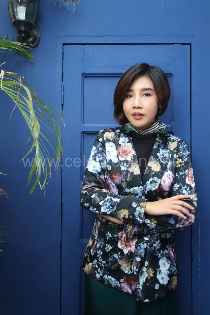 เสื้อคลุมลายดอกไม้สีดำ H&M เป็นเสื้อเชิ้ตด้านในคอเต่าสีดำ Uniqlo  กางเกงสีเขียวมรกต Zara basic เพิ่มความเก๋ด้วยผ้าพันคอลายสีเขียวและรองเท้าส้นสูง CHANEL