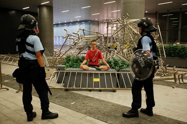 เจ้าหน้าที่ตำรวจยืนเฝ้าผู้ประท้วงที่นั่งประท้วงต่อต้านกฎหมายส่งตัวผู้ร้ายข้ามแดนไปจีนเมื่อคืนวันที่ 10 มิ.ย. 2019 (ภาพ รอยเตอร์ส)