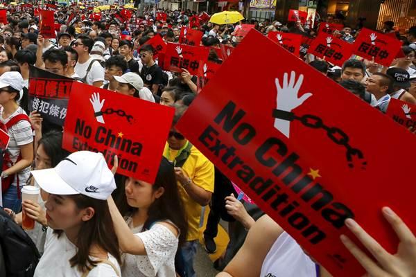 """กลุ่มผู้ประท้วงชูป้าย ไม่เอา """"กฎหมายส่งตัวผู้ร้ายข้ามแดนไปจีน"""" ในวันที่ 9 มิ.ย. 2019 (ภาพ เอพี)"""