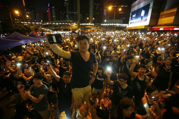 โทรศัพท์มือถือในมือของคนหนุ่มสาวผู้ชุมนุมประท้วงในฮ่องกง ซึ่งได้แสดงพลังทางการเมืองครั้งแรกจากการประท้วงรัฐบาล พ.ศ. 2557 หรือเรียก การปฏิวัติร่ม (Occupy Central) จนถึงการใช้ Telegram, WhatsApp และ Signal เทคโนโลยีการประท้วงครั้งล่าสุด ที่มีวิวัฒนาการขึ้นไปอีกระดับ (แฟ้มภาพรอยเตอร์ส, 2557)